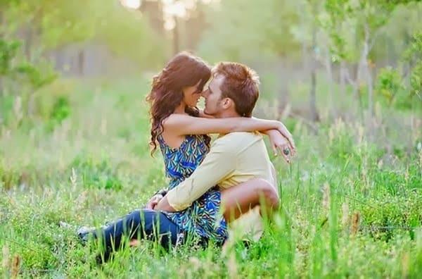 Парень обнимает и целует девушку на природе