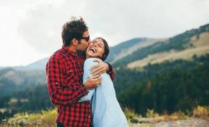 Парень целует девушку на фоне гор