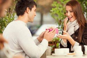 Парень вручает подарок красивой девушке
